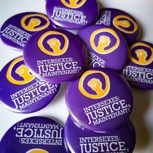"""badges violets et logo jaune poing levé, slogan """"intersexes justice maintenant !"""""""