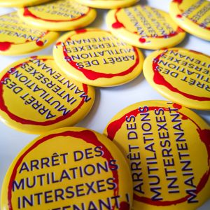 """badge fond jaune slogan encerclé de rouge """" arrêt des mutilations intersexes maintenant"""""""