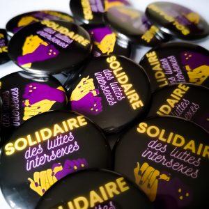 """fon noir, deux mains jaunes et violettes entrelacées, slogan """"solidaire des luttes intersexes"""""""