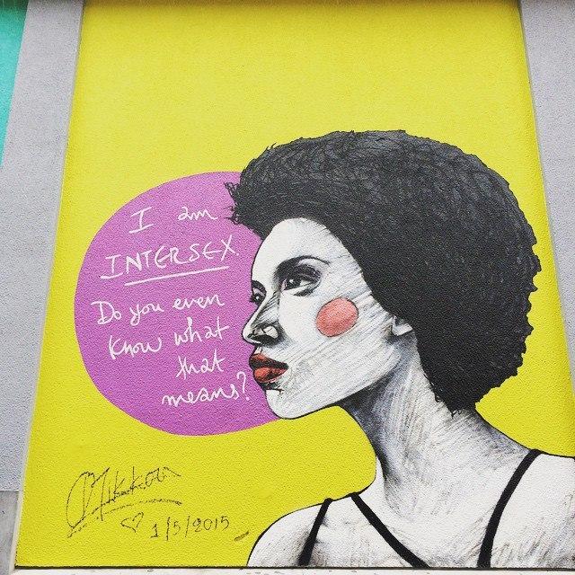 peinture murale : une personne avec un texte anglais indiquant je suis une personne intersexe, ais tu au moins ce que cela signifie ?