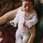 un nouveau né endormi dans les bras d'un parent