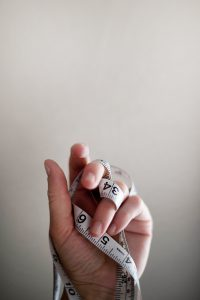 une main tenant un mètre mesureur