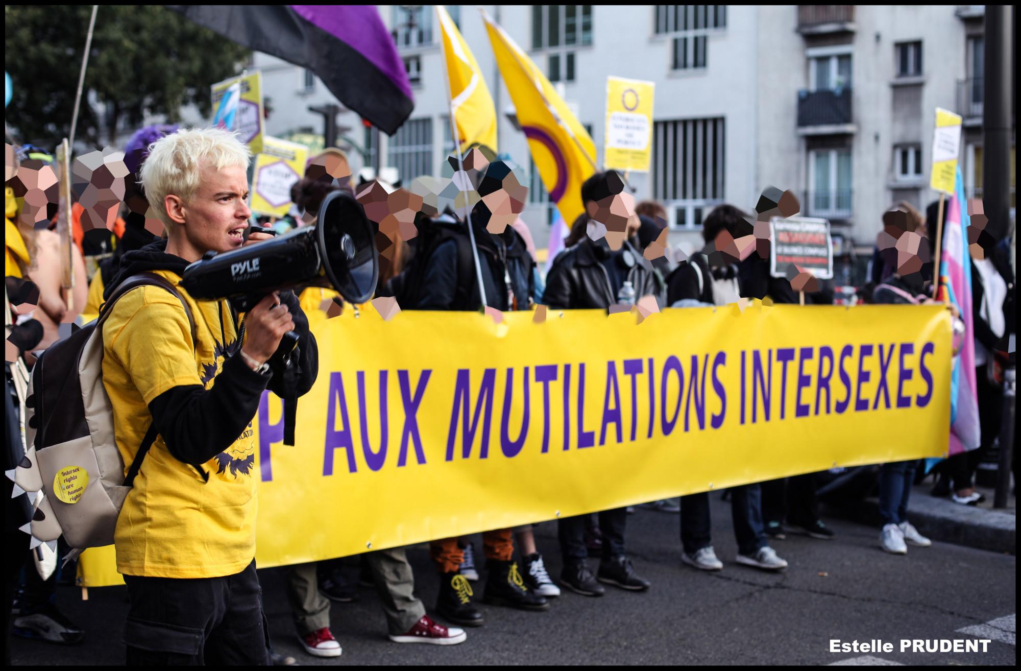 """en manifestation : au premier plan une personne tient un megaphone, devant une bannière annonçant """"stop aux mutilations intersexes"""""""