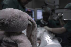 au premier plan, le doudou d'un enfant . A l'arrière, un enfant sur une table d'opération et des chirurgiens